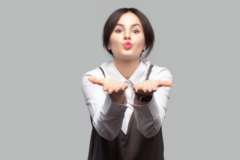 滑稽的美丽的年轻女人和与构成和收集的头发身分和送亲吻的棕色围裙画象白色衬衫的在 免版税库存照片