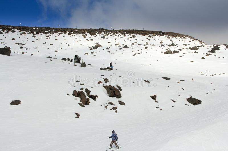 滑雪下坡从雪山上面的人们跟随滑雪小路 库存照片