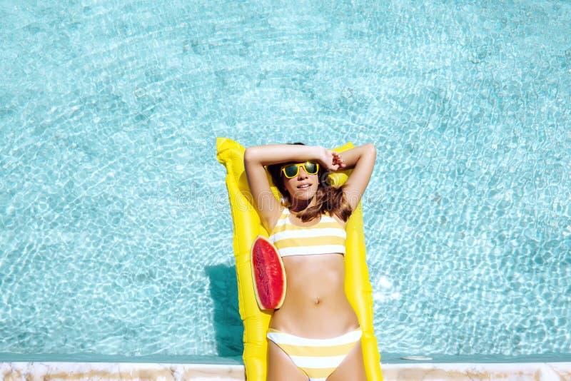 漂浮在海滩床垫和吃在旅馆水池的女孩西瓜 免版税库存照片