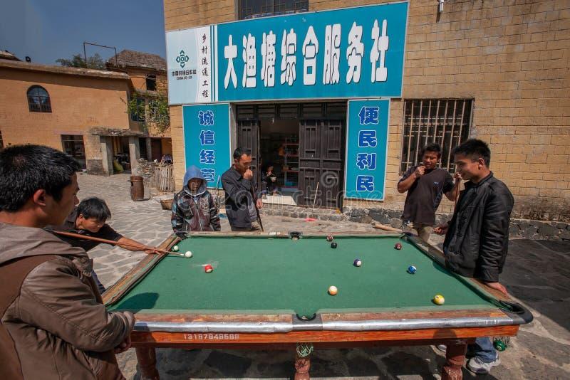 演奏台球的中国人在庭院在老村庄在中心,在工作以后享受活动 云南,中国 库存照片
