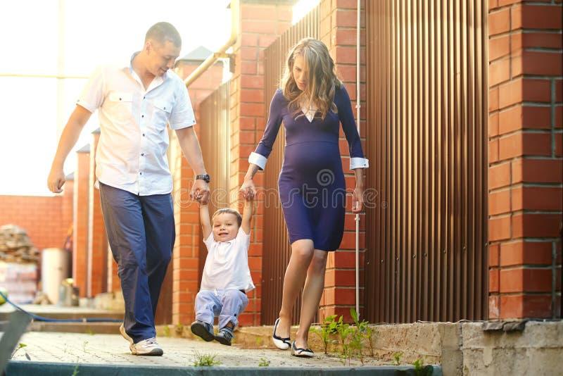 演奏家庭户外 有儿子的年轻父母在夏天 妈妈、爸爸和孩子 免版税库存照片