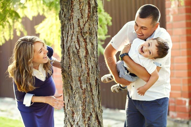 演奏家庭户外 有儿子的年轻父母在夏天 妈妈、爸爸和孩子 库存图片