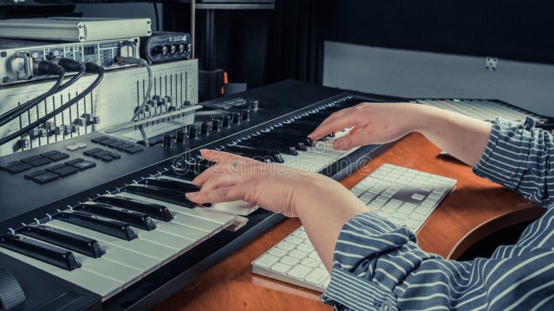演奏密地键盘合成器的女性音乐家在录音室,在手上的焦点 妇女胳膊音乐戏剧独奏或新 免版税库存照片