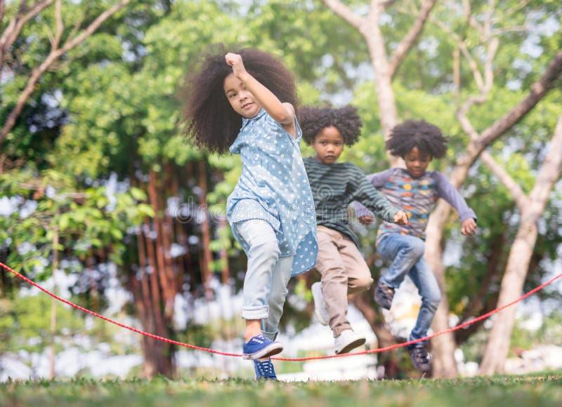 演奏在绳索的孩子跃迁在公园在晴朗的夏日 免版税库存照片