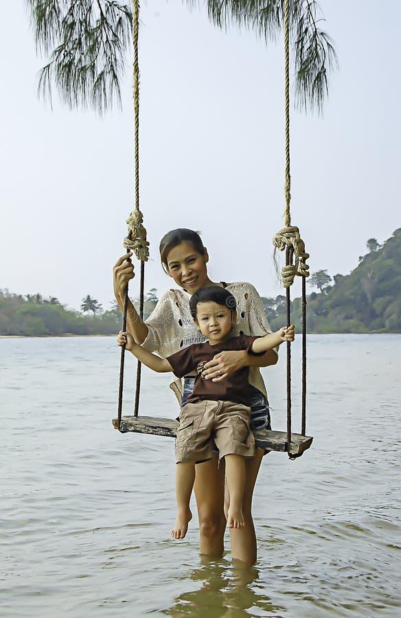 演奏摇摆椅子的母亲和儿子画象在海 库存图片