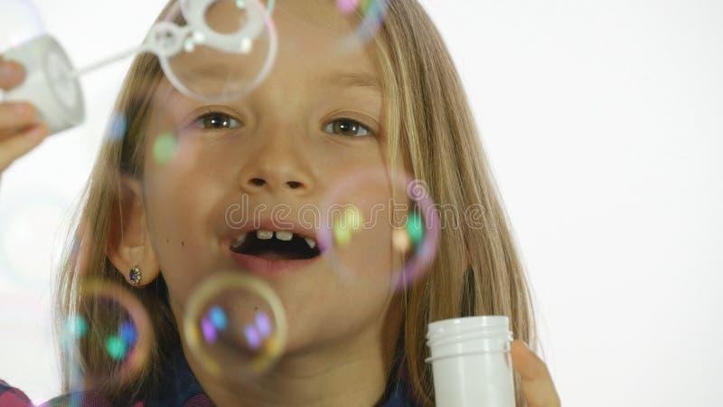 演奏肥皂泡,愉快的微笑的女孩吹的气球,慢动作的孩子 库存图片