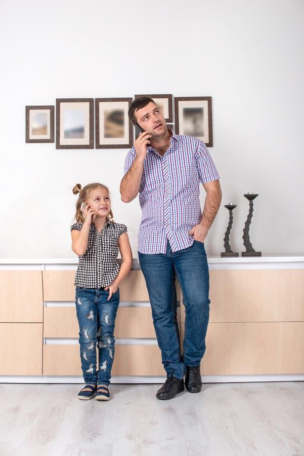 演播室射击了女孩和她的爸爸在家站立和谈在电话同一个方式 女儿仿效她的父亲 免版税库存图片