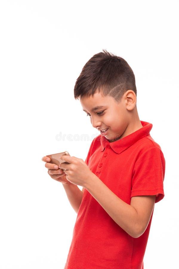 演播室有时兴时髦理发写的男孩穿红色衬衣的被射击一个微笑的和男孩sms在白色的电话 库存照片