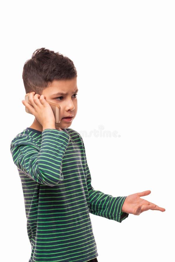 演播室被射击一个小严肃的男孩谈话在白色背景的电话 免版税库存照片
