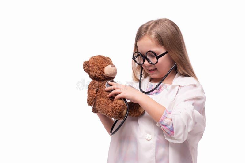演播室被射击一件白色医疗褂子的一个小微笑的女孩有对待女用连杉衬裤的听诊器的涉及白色背景与 图库摄影