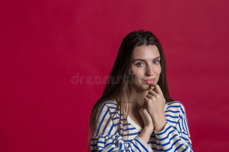 演播室被射击一可爱的美女对空的红色演播室墙壁 免版税库存照片