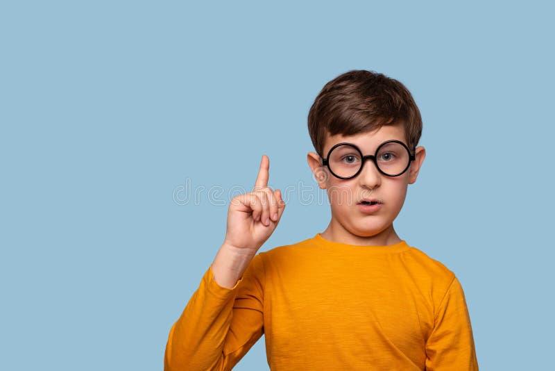 演播室被射击证明某事的圆的玻璃的一个滑稽的男孩通过举他的食指,隔绝在与拷贝空间的蓝色 图库摄影