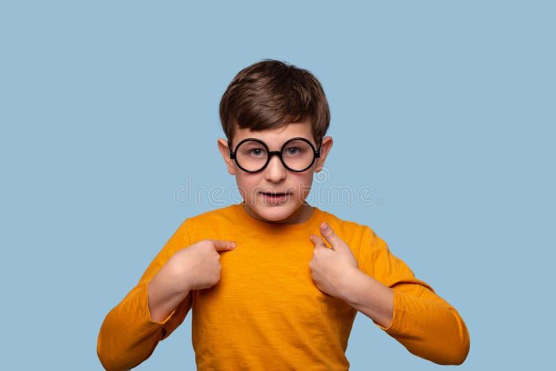 演播室证明某事的被射击一个严肃的男孩指向他的手他自己,隔绝在与拷贝空间的蓝色 免版税图库摄影
