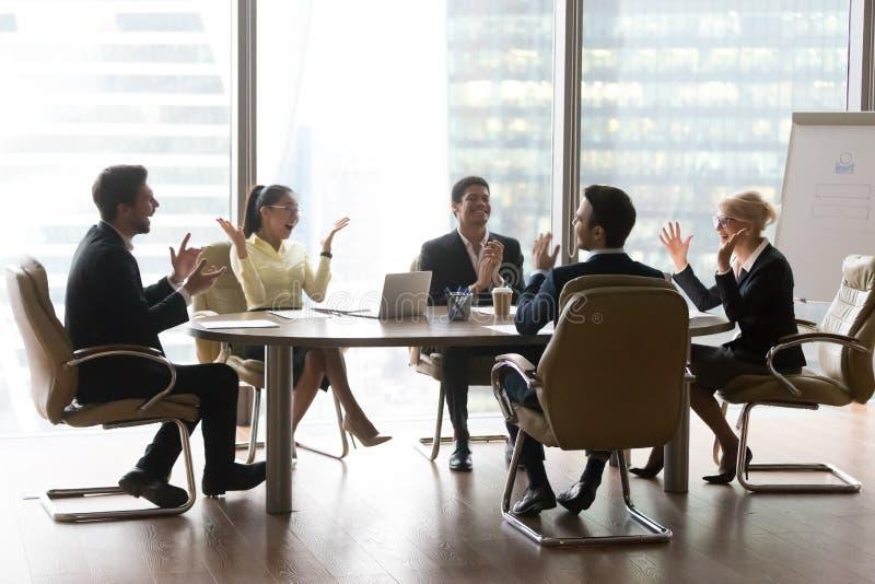 激动的不同的队委员会董事在办公室庆祝企业成功 图库摄影