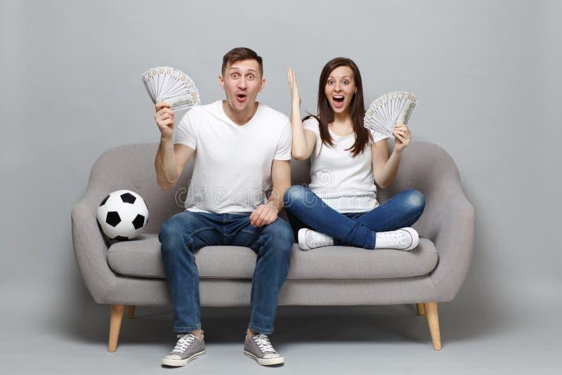 激动的夫妇妇女人足球迷在美元钞票欢呼金钱,现金支持喜爱的队藏品爱好者  免版税库存图片