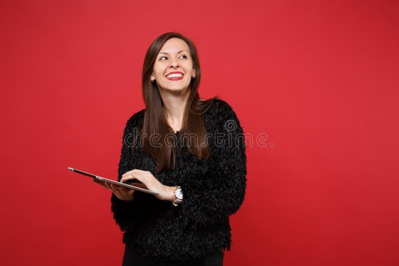查寻,使用平板电脑计算机的黑毛皮毛线衣的微笑的沉思年轻女人隔绝在明亮的红色墙壁上 库存图片