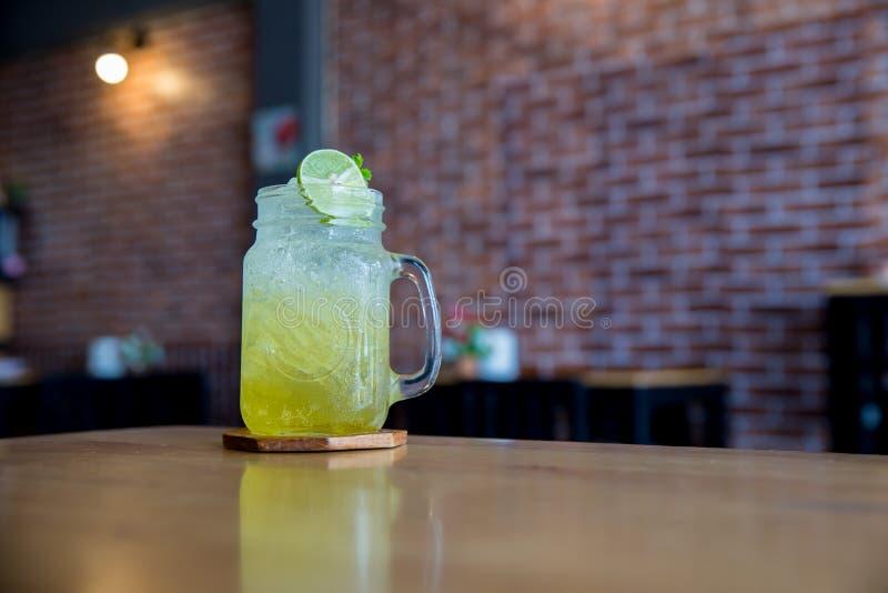 柠檬汁用在木桌上的蜂蜜 在玻璃的柠檬嘶嘶响 饮料夏天蜂蜜和柠檬苏打  免版税库存照片