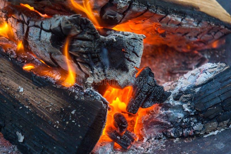 柴火炭烬的关闭与火焰和烟 免版税图库摄影