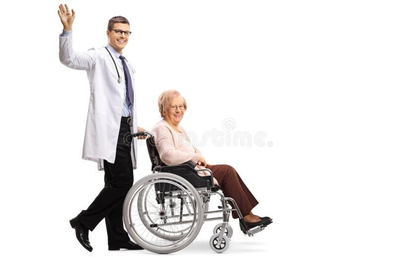 挥动和推挤轮椅的年轻微笑的正面男性医生一名残疾资深妇女 库存照片