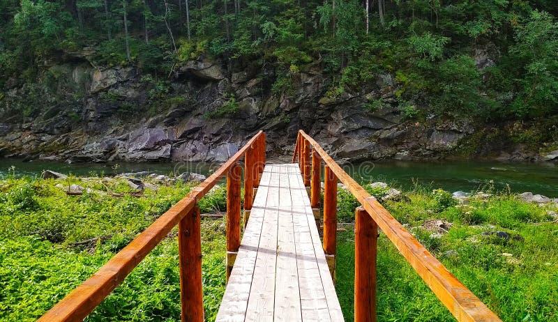 木桥在有岩石的山河在背景中 库存图片
