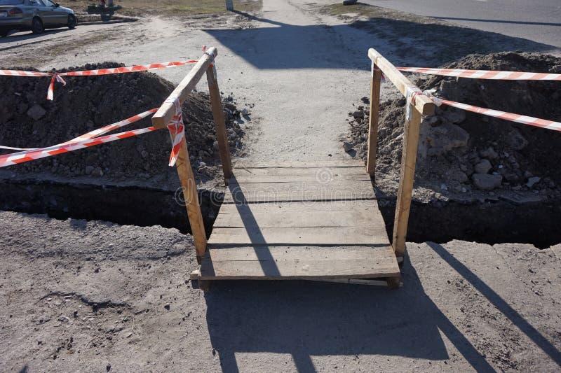 木桥通过沟槽被开掘修理通信 库存图片