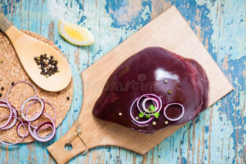 未加工的牛肉肝脏片断在一个切板、葱、柠檬和香料的烹调的在一张木桌上 库存照片