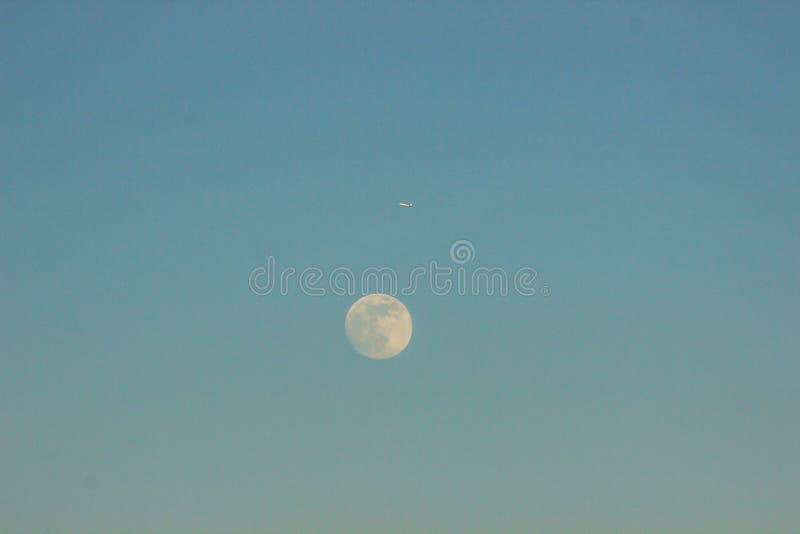 月亮反对天空蔚蓝和在平面旁边飞行 它得到黑暗,日落和月出 日夜变动 库存图片
