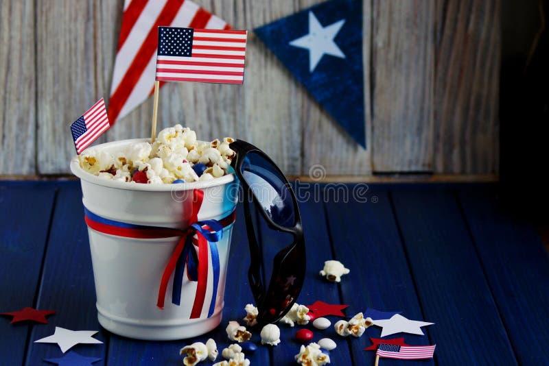 7月4日爱国玉米花在有美国国旗的一个白色桶在蓝色木背景 美国独立日 库存照片