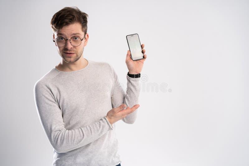 指向与他的在他的在白色背景的智能手机屏幕上的手指的愉快的年轻人画象  免版税库存图片