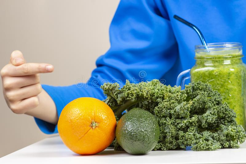 指向健康圆滑的人瓶子的孩子手和菜和果子在桌上 库存照片