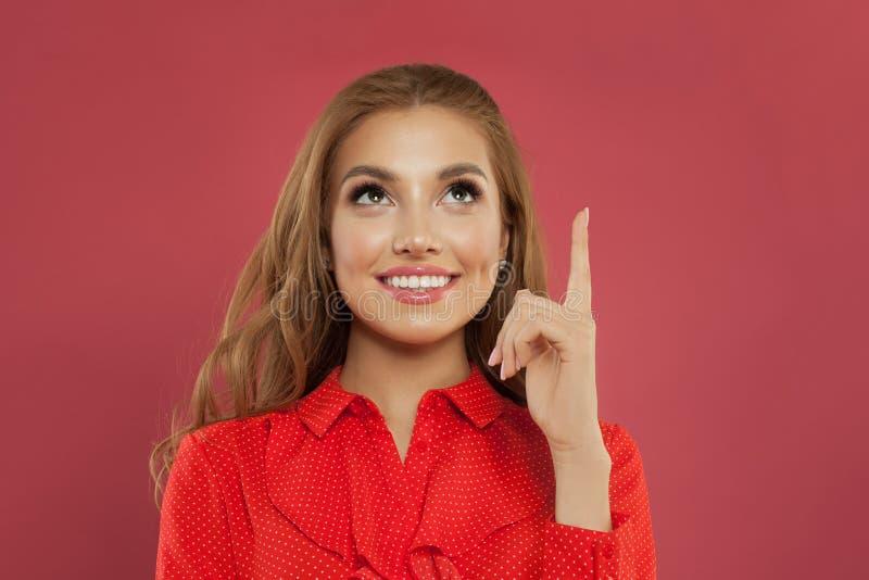 指向在五颜六色的桃红色背景画象的愉快的年轻美丽的快乐的妇女 查寻学生的女孩指向手指和 免版税库存照片