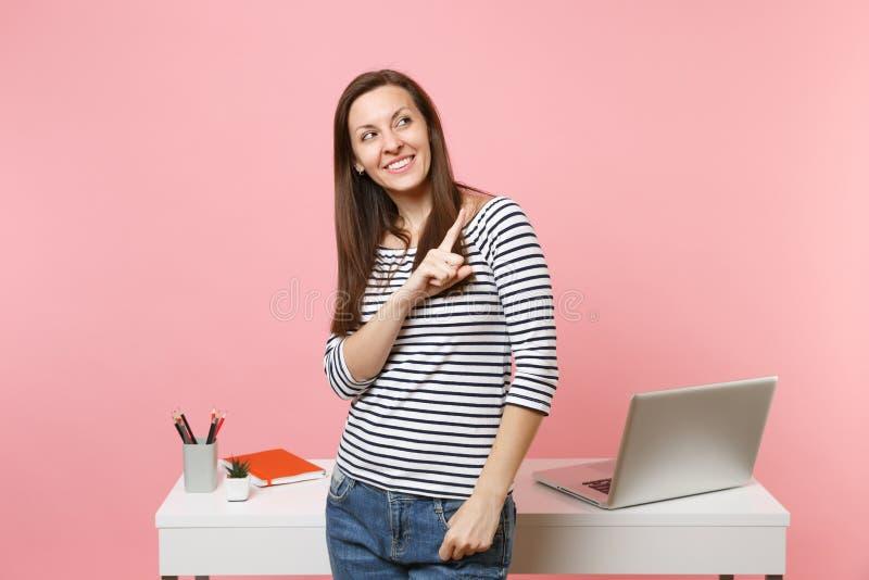 指向食指在旁边工作和站立在有在粉红彩笔隔绝的个人计算机膝上型计算机的白色书桌附近的年轻微笑的妇女 免版税库存照片