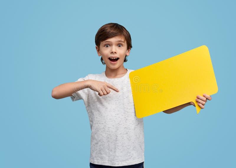 指向黄色讲话泡影的惊奇的孩子 免版税库存照片