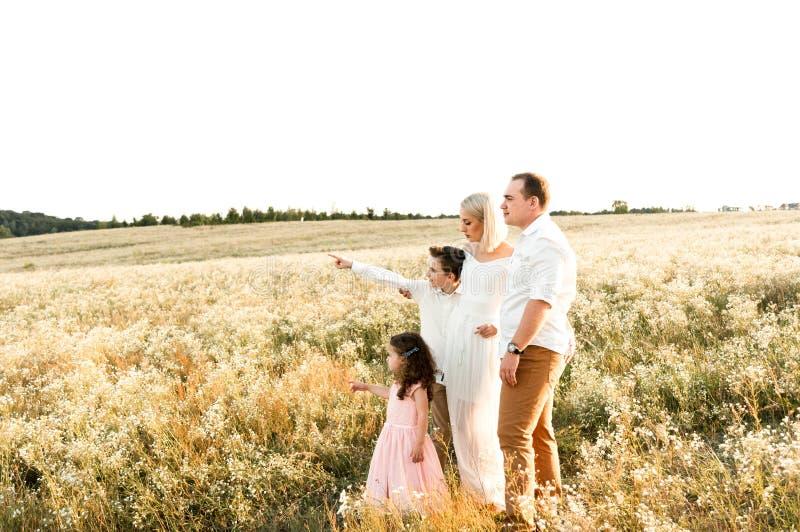 有两个孩子的美丽的年轻家庭看某事在天空 图库摄影