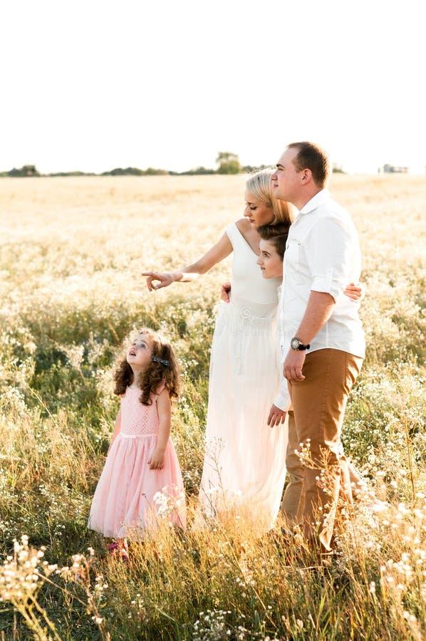 有两个孩子的美丽的年轻家庭看某事在天空 免版税库存照片