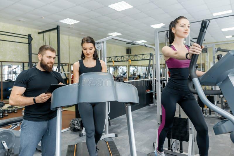 有个人教练员的年轻微笑的健身妇女踏车的一个成人运动人在健身房 体育,配合,训练, 免版税库存照片