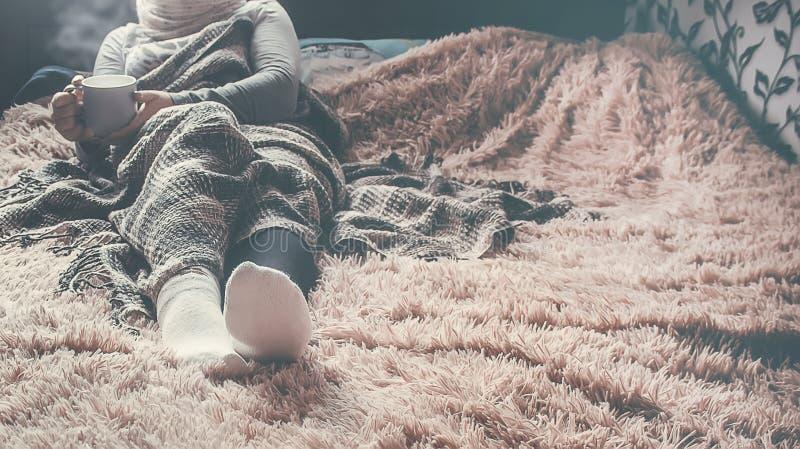 有一个杯子的一个女孩在毯子下的naya谎言 选择聚焦 库存照片