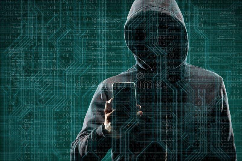 有一个智能手机的匿名计算机黑客在抽象数字背景 在面具和敞篷的被遮暗的黑暗的面孔 数据 免版税图库摄影