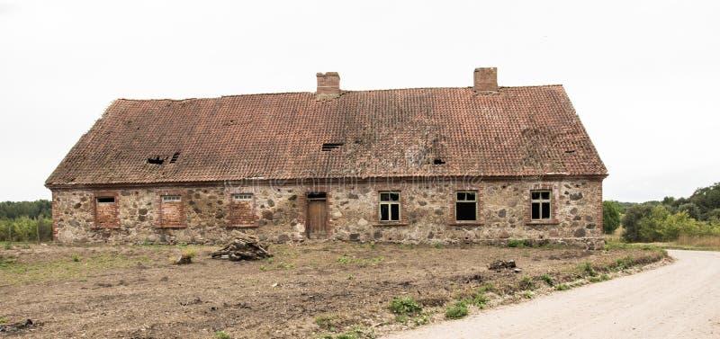 有一个瓦屋顶的一个老被放弃的石房子在村庄 免版税库存图片