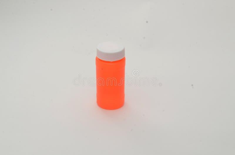 有一个白色盒盖的一个空的橙色瓶在简单的白色 库存图片