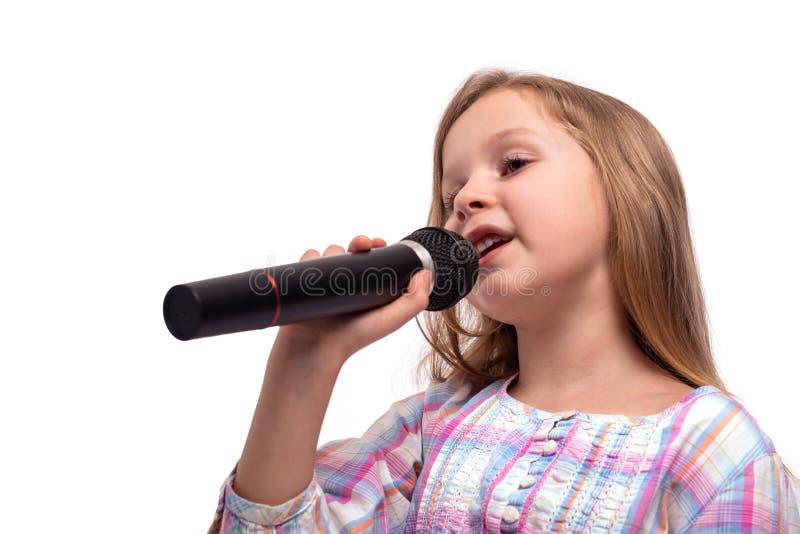 有一个话筒的女孩在她的手上唱歌曲,隔绝在与拷贝空间的白色 免版税图库摄影