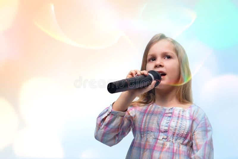 有一个话筒的女孩在她的手上唱歌曲,隔绝在与拷贝空间的白色 图库摄影