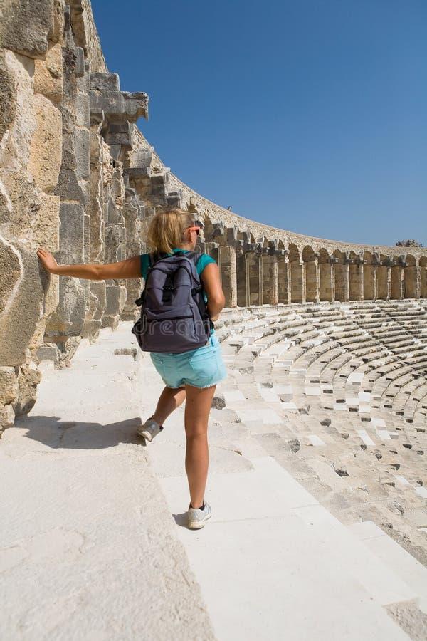 有一个背包的女孩旅客在古老剧院的疆土 免版税图库摄影