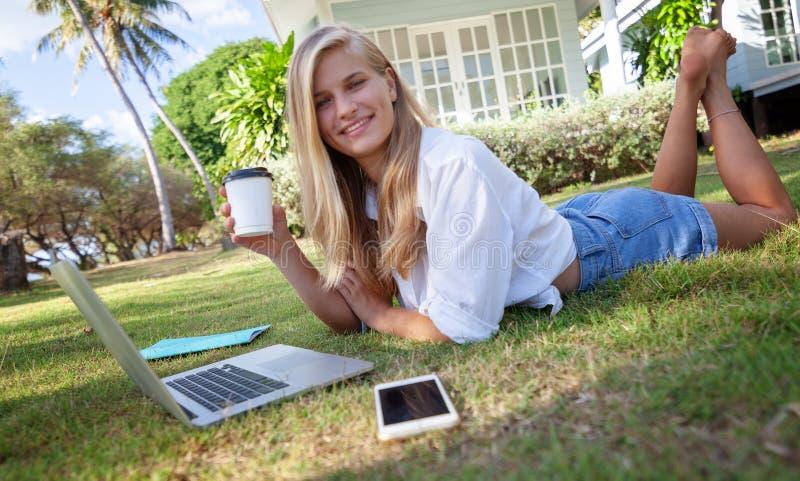 有一台膝上型计算机的美丽的白肤金发的女孩在绿色草坪、教育和遥远的工作 免版税库存照片