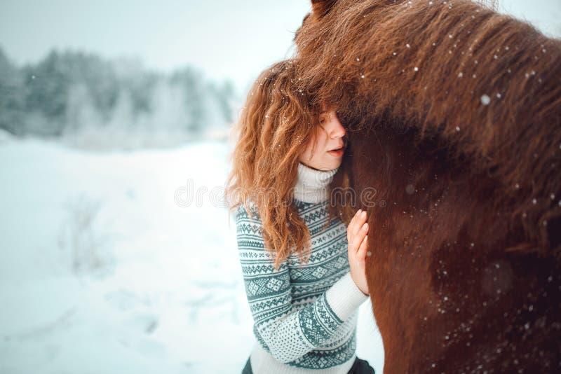 有一匹马的红色顶头女孩在雪的领域在冬天 免版税库存照片