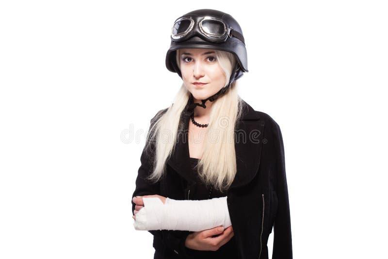 有一条断胳膊的女孩在膏药,佩带的摩托车盔甲 免版税库存照片