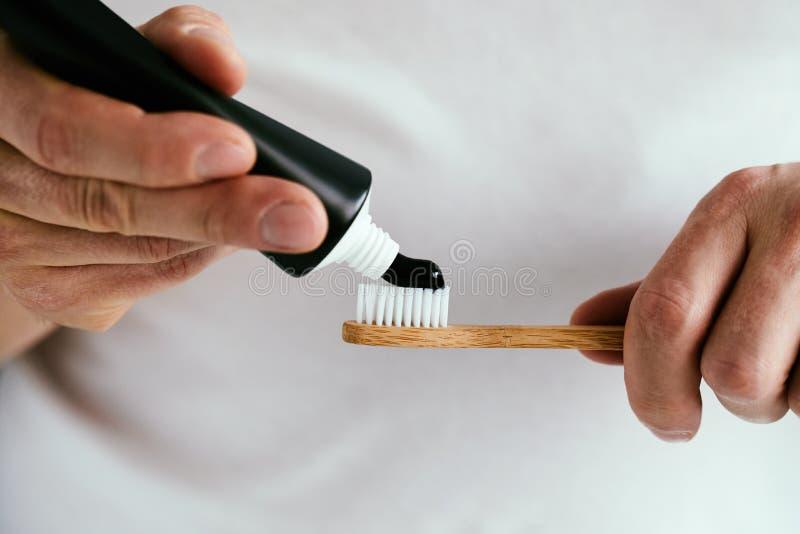 有一支黑牙膏和一把竹牙刷的男性手 库存照片