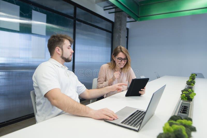 有一种片剂和一个人的正面女孩有笔记本工作的在办公室 一个人显示片剂的一名妇女 库存图片