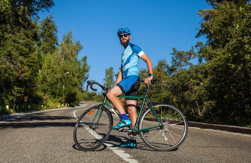 有一辆自行车的一个人在山 在用森林盖的山的路 图库摄影