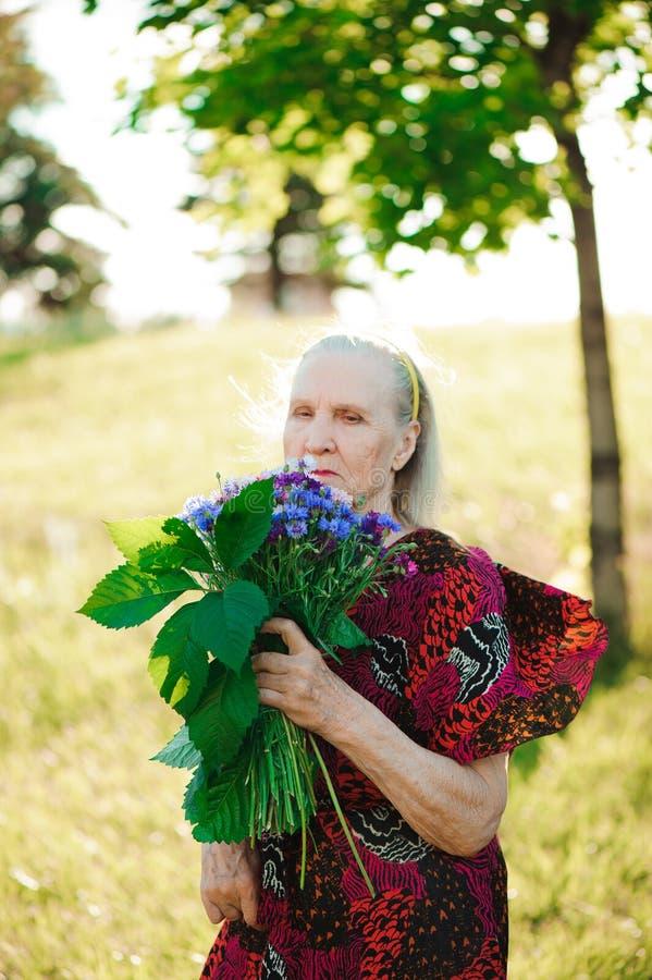有一花束的80岁的妇女在她的手上 库存图片